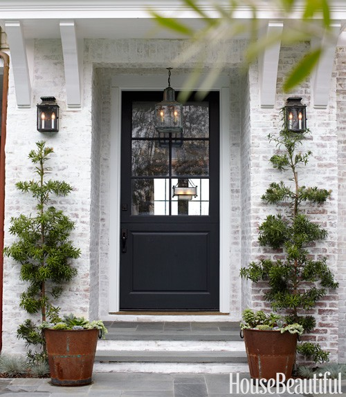 Beautiful outdoor entryway with white brick and a black door from House Beautiful.  ||  Friday Favorites at www.andersonandgrant.com